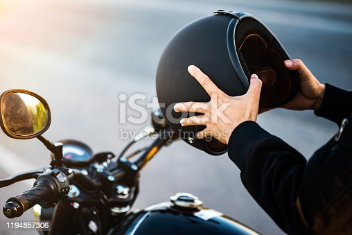 Motorcycle couple holding helmets in hands .