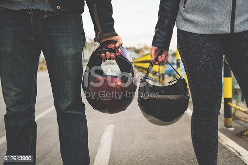 Motorcycle couple holding helmets in hands on the road