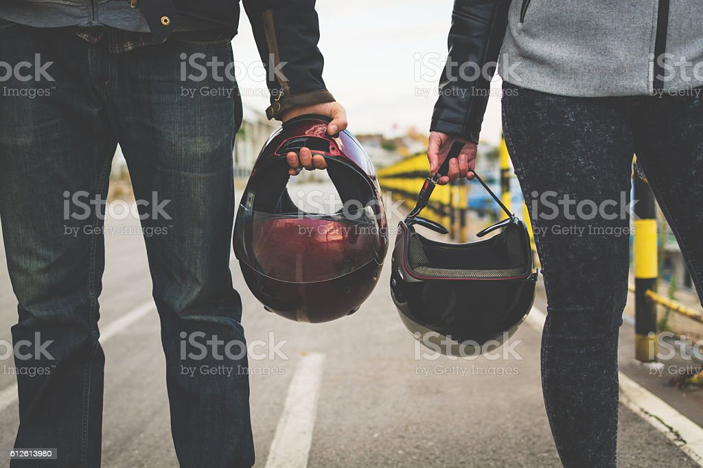 Motorcycle couple holding helmets in hands stock photo