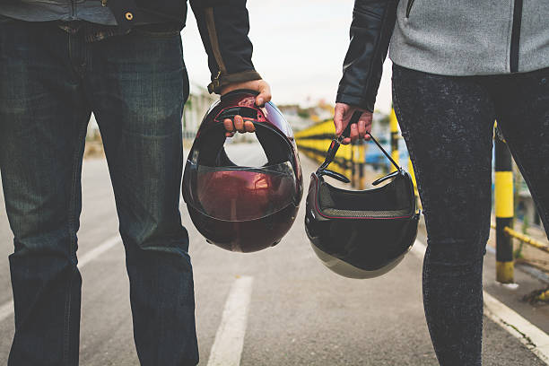 Motorcycle couple holding helmets in hands - foto stock