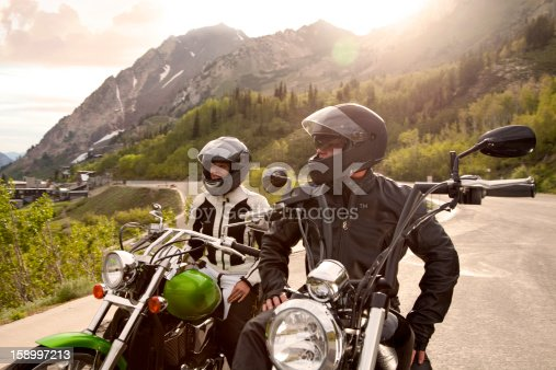 Motorcycle couple parked and enjoying view of snow capped mountains