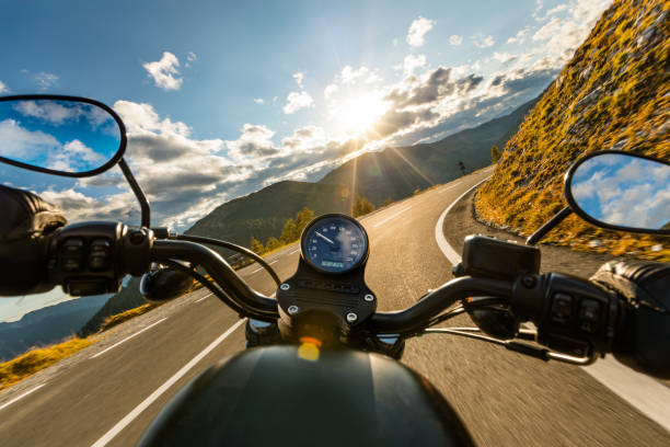motorcycle driver riding in alpine highway, handlebars view, austria, europe. - motorcycle stock photos and pictures