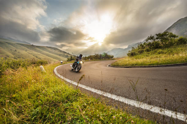 Motorcycle driver riding in Dolomite pass, Italy, Europe. stock photo