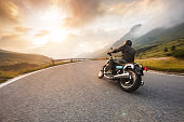 istock Motorcycle driver riding in Dolomite pass, Italy, Europe. 1171675830