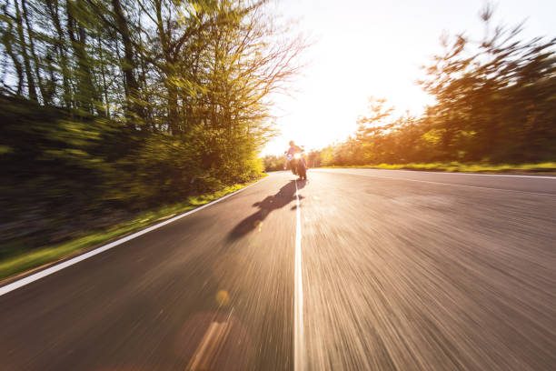 Motorcycle driver riding in European road stock photo