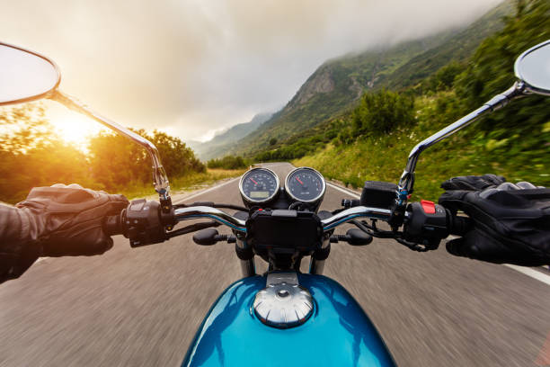 Motorcycle driver riding in mountains stock photo