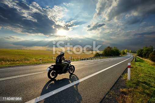 Motorcycle driving on the asphalt road in rural landscape at sunset with dramatic clouds