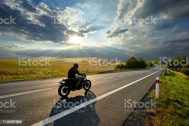 Photo of Motorcycle driving on the asphalt road in rural landscape at sunset with dramatic clouds