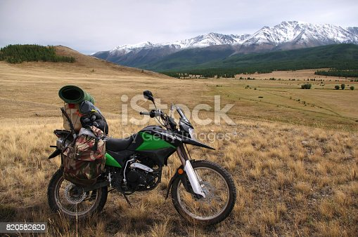 istock Motorcycle enduro traveler with suitcases on yellow grass field in a mountain valley in cloudy weather on the background of snow glacier ranges Plateau Ukok Altai mountains Siberia Russia 820582620