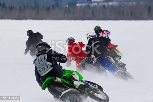 A group of men compete in a winter motorcycle ice race.