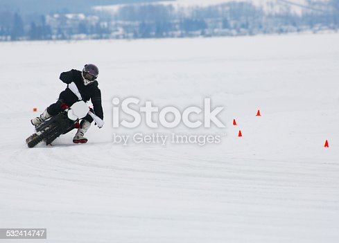 A man rides a corner at a winter motorcycle ice race on a frozen lake.