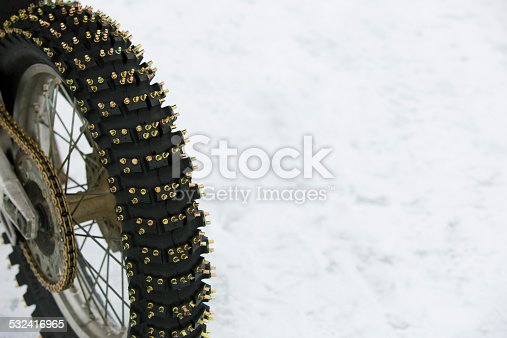 A close up view of a rear motorcycle tire with metal studs for riding on the ice and snow in the winter.
