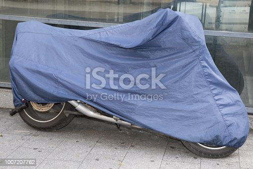 istock motorcycle in the street protected by a protective cover 1007207762