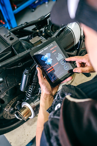 Mechanic reviewing motorcycle with a tablet app in the workshop