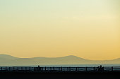 Motorcycle on the highway bridge during the dawn against the backdrop of mountains and the sea