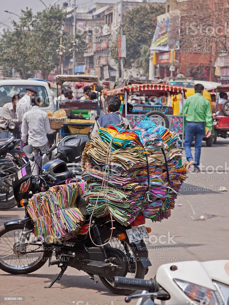 Motorcycle piled high with textiles in old Delhi, India stock photo