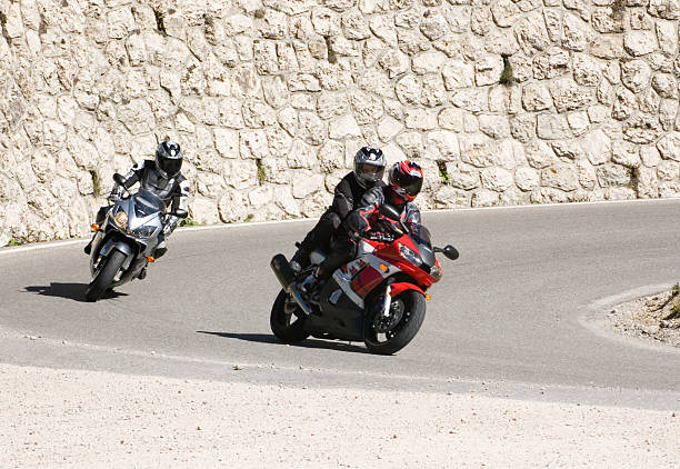 Motorcycle pursuit Going down a switchback in the Dolomites. three wheel motorcycle stock pictures, royalty-free photos & images