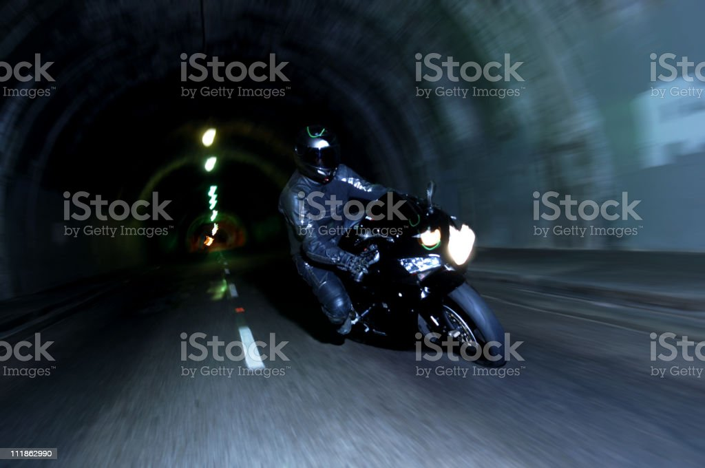 Motorcycle Racing Through Tunnel at Night stock photo