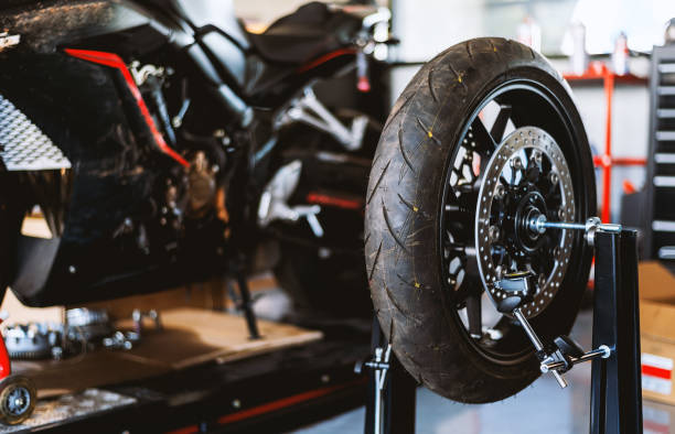 motorcycle  repair. closeup wheel balancing machine at tyre service center with soft-focus and over light in the background – zdjęcie
