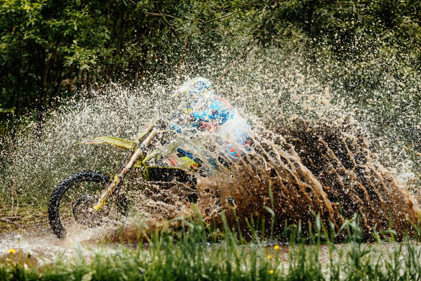 motorcycle rider crosses puddle splashes of water and dirt - bike tire tracks foto e immagini stock