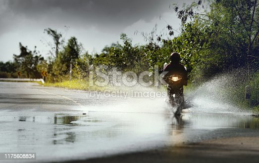 istock Motorcycle run through flood water after hard rain with water spray from the wheels,stop action. 1175608834