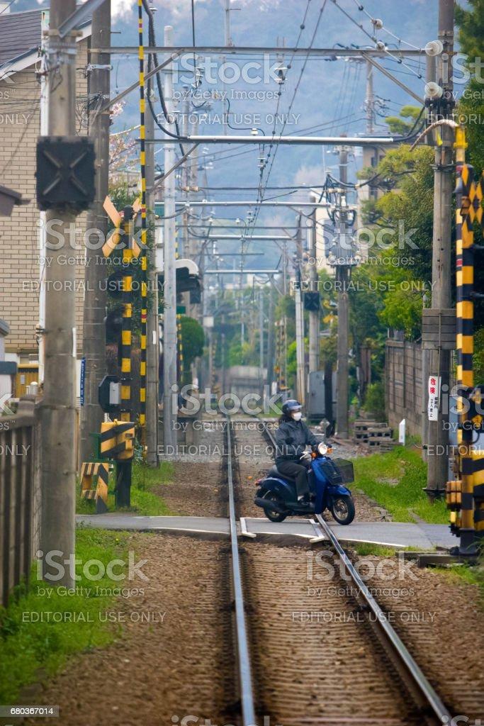 Motorcycle (motor bike) running cross the railroad at Kamakura royalty-free stock photo