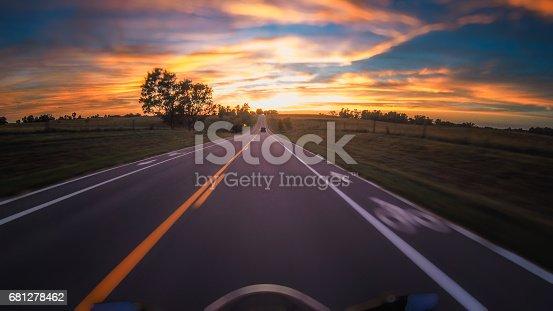 Motorycle speeding down highway toward the sunset