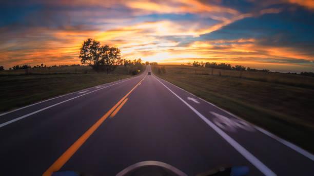 Motorcycle speeding into the sunset stock photo