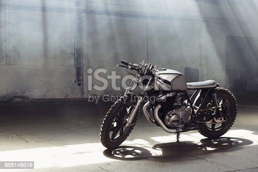 istock motorcycle standing in dark building in rays of sunlight 858148616