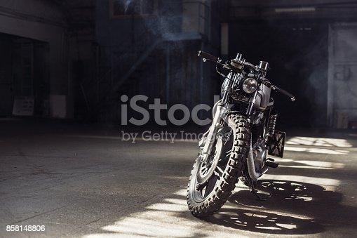 istock motorcycle standing in dark building in rays of sunlight 858148806