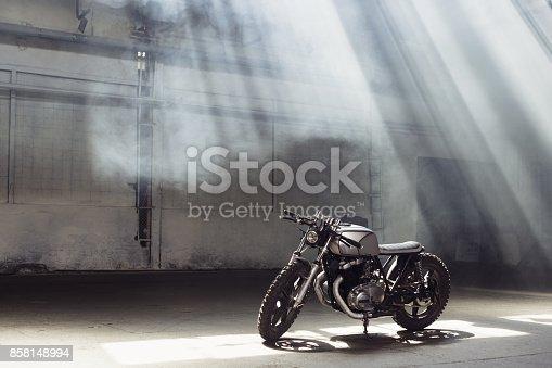 istock motorcycle standing in dark building in rays of sunlight 858148994