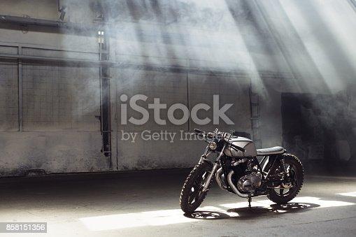 istock motorcycle standing in dark building in rays of sunlight 858151356