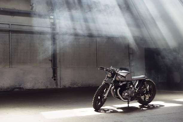 motorcycle standing in dark building in rays of sunlight - motorcycle stock photos and pictures