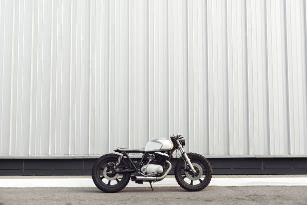 motorcycle standing in dark building in rays of sunlight stock photo