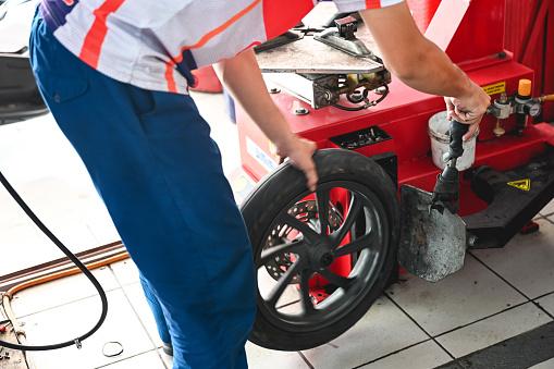 Unrecognizable mechanic motorcycle tire balancing, Nikon Z7