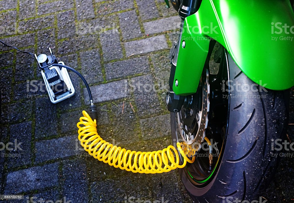 Motorcycle tire being checked for pressure and inflated stock photo
