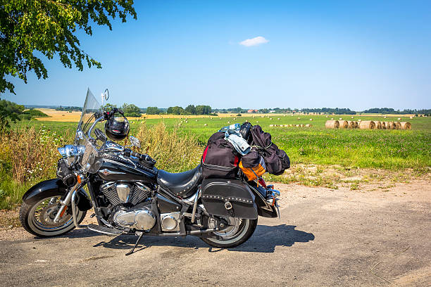 Motorcycle with luggage during the journey Szczecin, Poland - August 07, 2015: Heavy customized Kawasaki VN 900 Classic with luggage during the journey in side of the  road through the cultivated fields in a sunny day, Warmia, Poland  kawasaki heavy industries stock pictures, royalty-free photos & images
