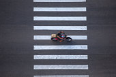 Large zebra crossing in the city with motorcycle running on street
