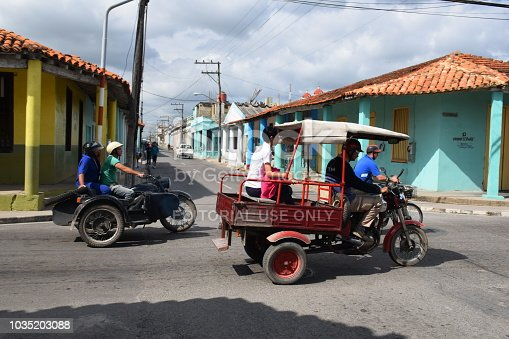 Santa Clara, Cuba - January 20th, 2016: Side shot on the motorcycles and tricycle on Cuban street. The old-styled vehicles from 60s are the ones of the most popular vehicles in Cuba.