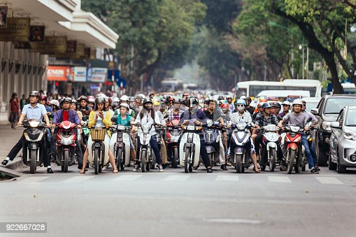 istock Motorcycles got traffic jam on the road with green trees in background at Hanoi, Vietnam. 922667028