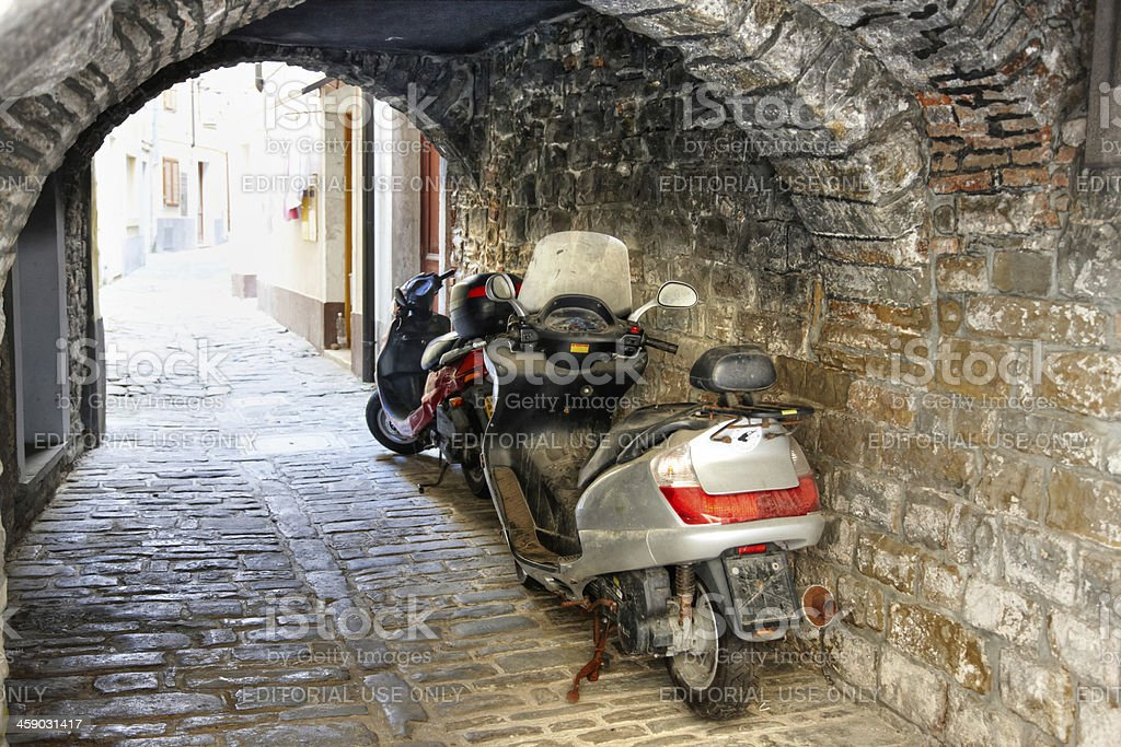 Motorcycles parked under archway on Slovenian street royalty-free stock photo