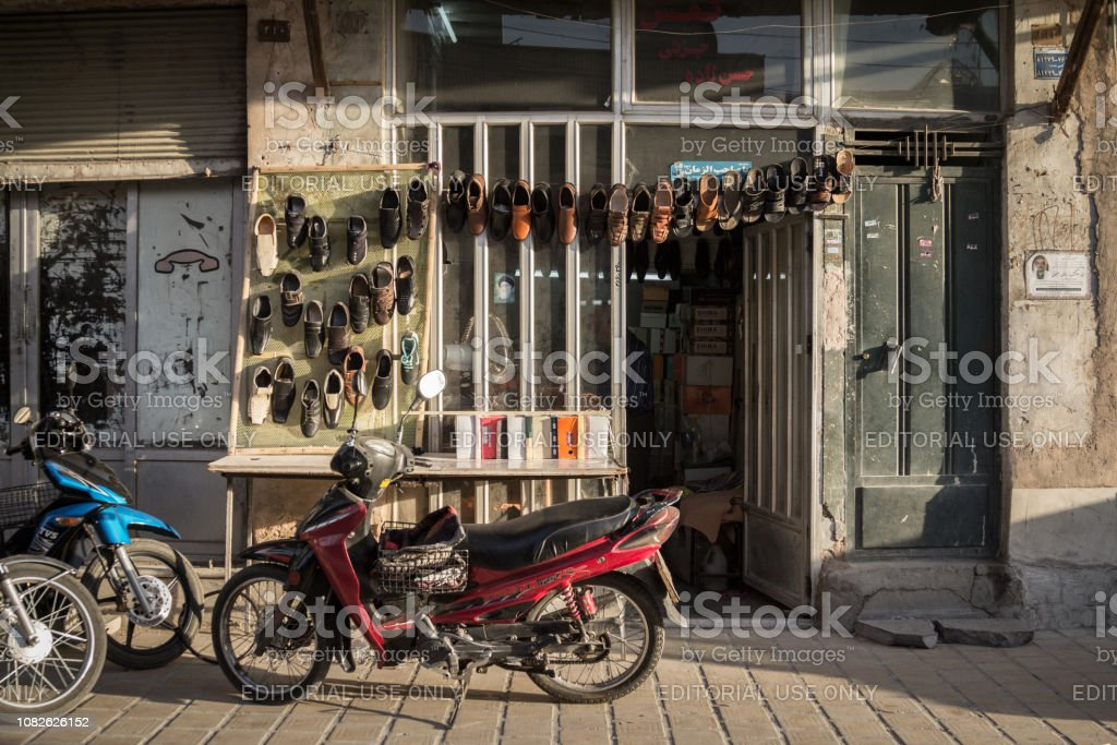 Motorcycles standing in front og a shoemaker shop, with shoes hand in front. The Isfahan bazar is one of the symbols of the city stock photo