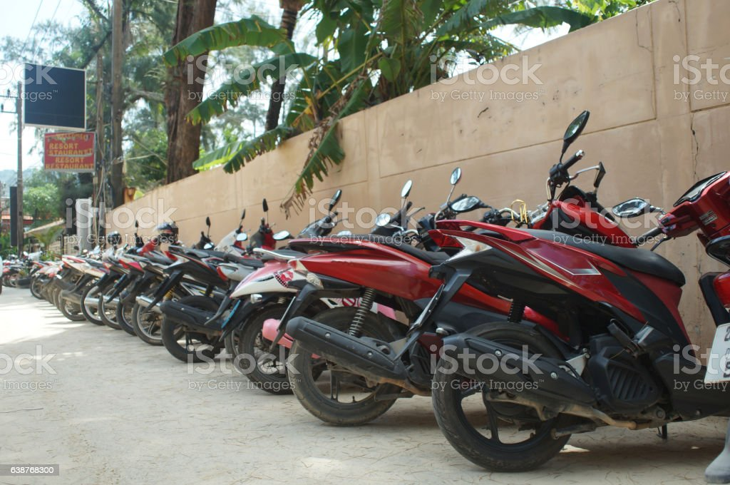 motorcycles standing in the row on asphalt closeup stock photo