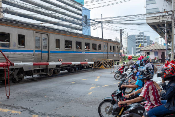 motorcycles wait at a level crossing in bangkok, thailand - motorbike, umbrella stock photos and pictures
