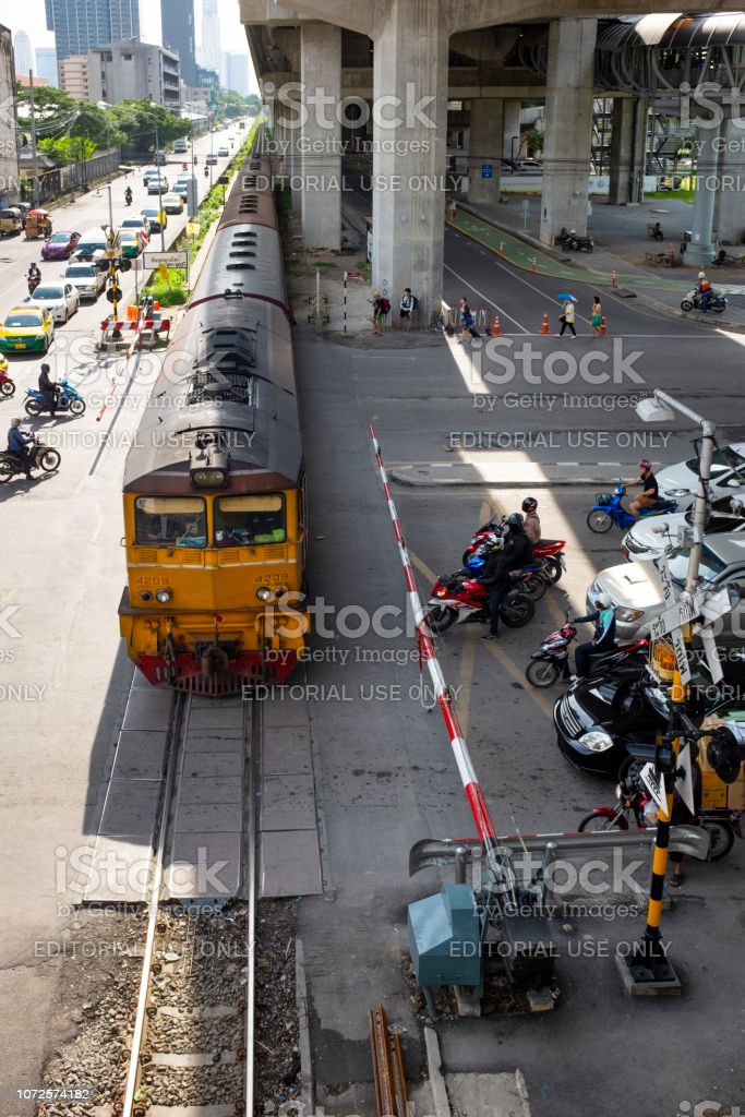Motorcycles Wait At A Level Crossing In Bangkok, Thailand stock photo
