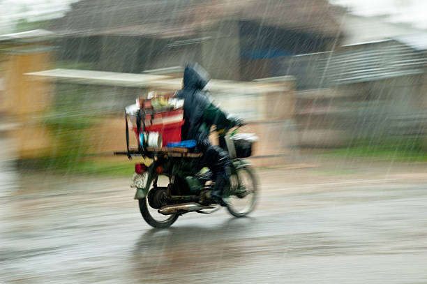 motorcycling through a rain storm in vietnam - motorbike, umbrella stock pictures, royalty-free photos & images