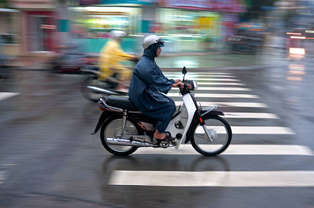 motorcycling through a storm in vietnam - motorbike, umbrella stock pictures, royalty-free photos & images
