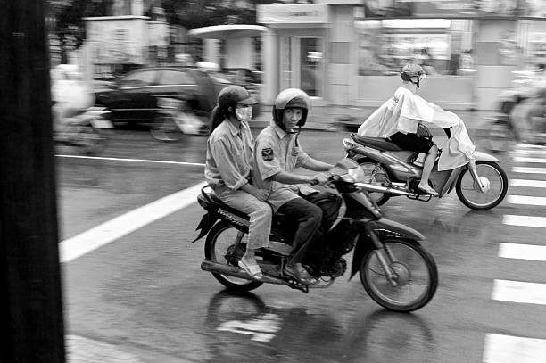 motorcycling through a storm in vietnam - motorbike, umbrella stock photos and pictures