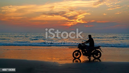 istock Motorcyclist at sunset on the beach. 469718093