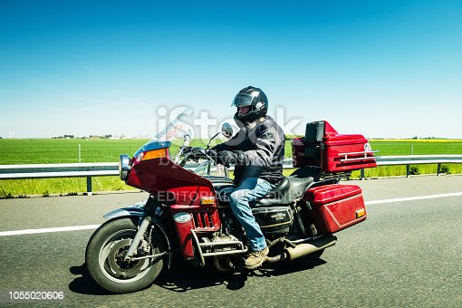 FRANCE - MAY 5, 2016: Motorcyclist driving vintage Honda Goldwing GL1000 motorcycle French highway - holiday travel style vintage lifestyle